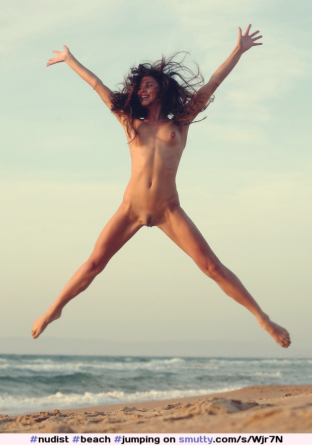 Jumping nude model in a field