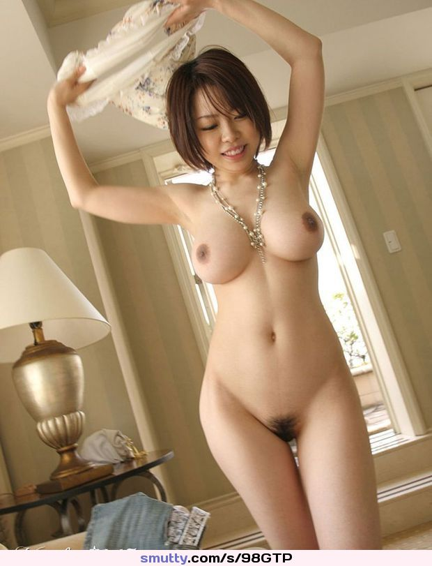 Playful Asian slut happily strips her clothes to show off her fat tits and natural bush.